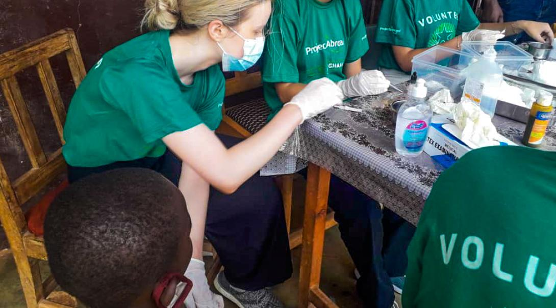 Projects Abroad volunteer cleans a child's wound in rural Ghana